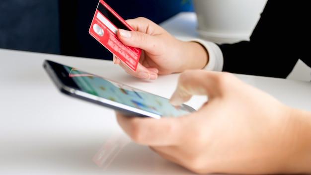 Молодая женщина, держащая банковскую кредитную карту, делая покупки в интернете на смартфоне. концепция покупок в интернете и электронной коммерции.