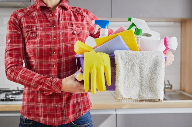 Young woman holding  basin of cleaning supplies and product  in kitchen