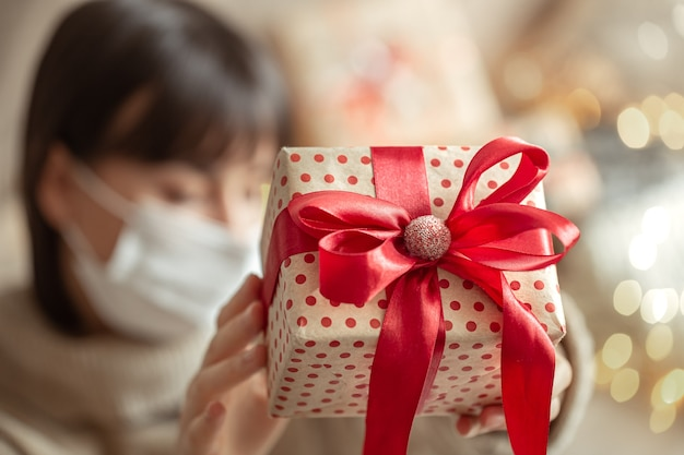 Young woman holding a beautifully wrapped christmas gift. concept of celebrating christmas during coronavirus pandemic.