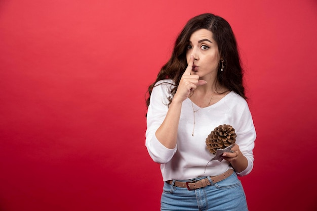 Giovane donna che tiene una grande pigna di natale e dà il segno del silenzio. foto di alta qualità