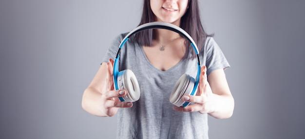 大きなヘッドフォンを持った若い女性