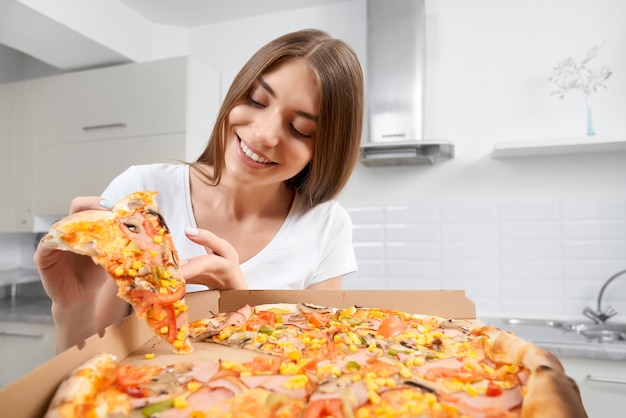 Young woman holding big pizza and eating piece