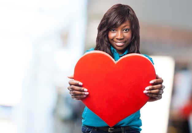 Giovane donna che tiene un grande cuore rosso