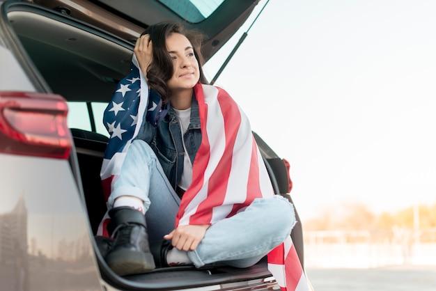 Молодая женщина держит большой флаг сша в багажнике