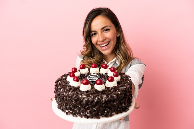 Young woman holding birthday cake over isolated pink background