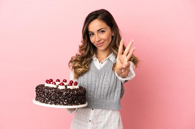 幸せな孤立したピンクの背景の上にバースデーケーキを保持し、指で3を数える若い女性