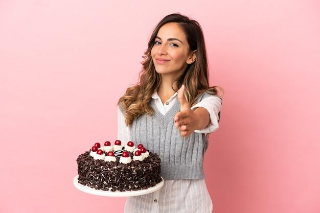 Молодая женщина, держащая торт ко дню рождения на изолированном розовом фоне, пожимая руку для заключения хорошей сделки