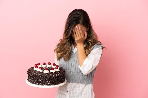 피곤하고 아픈 표정으로 고립 된 분홍색 배경 위에 생일 케이크를 들고 젊은 여자