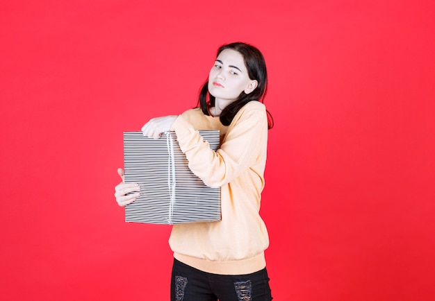 Young woman holding birthday gift box while wearing yellow shirt