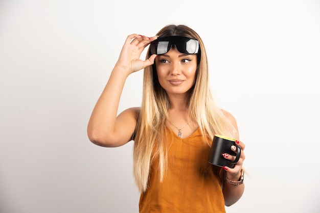 Young woman holding black cup and wearing goggles.