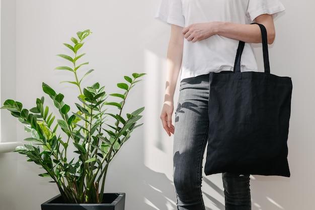 Молодая женщина, держащая черный текстильный эко-мешок против белой стены.