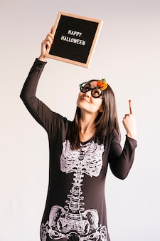 Young woman holding a black vintage letter board with happy halloween sign.  lifestyle indoors. skeleton costume