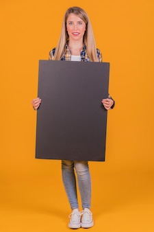 A young woman holding blank black placard in hand against an orange background