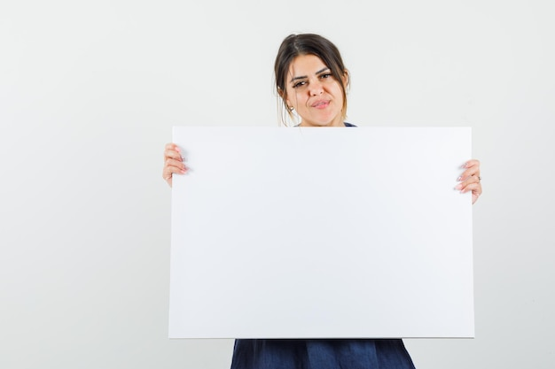 Young woman holding blank canvas in dress and looking confident