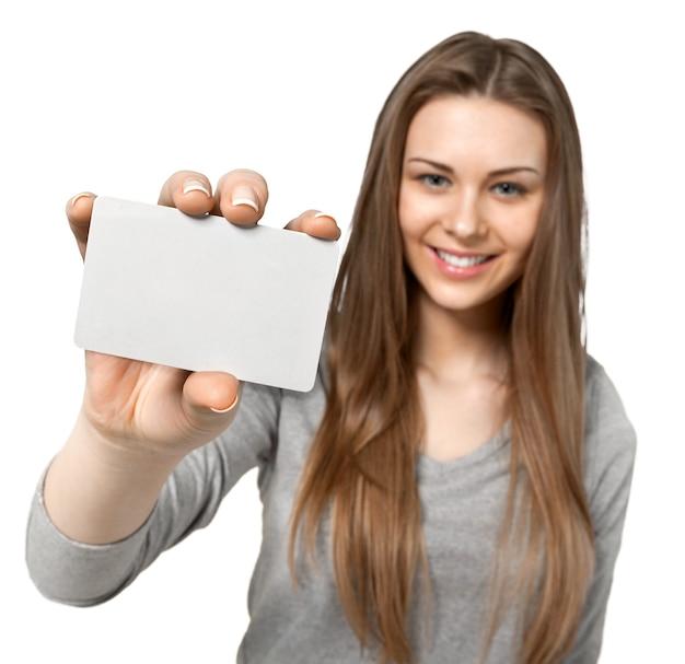 空白のカードを保持し、それをカメラに見せて若い女性