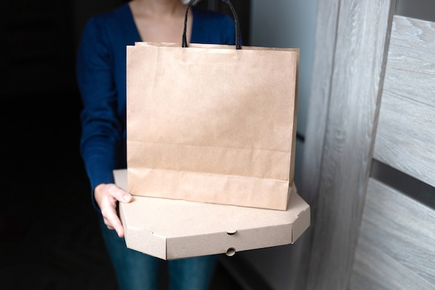 Young woman holding blank cardboard pizza box and paper shopping bag.