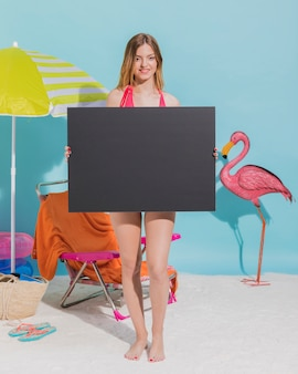 Young woman holding blank dark sheet of paper