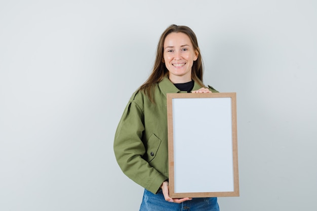Young woman holding blank frame in green jacket and looking satisfied. front view.