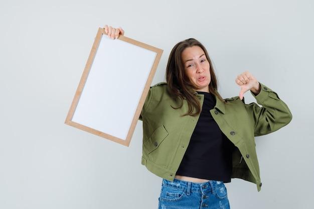 緑のジャケットで親指を下に表示し、不満を見て、正面から空白のフレームを保持している若い女性。