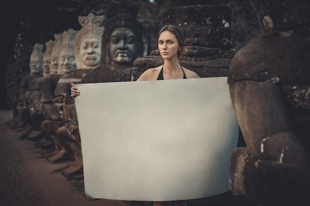 Young woman holding blank placard in dark mystic location