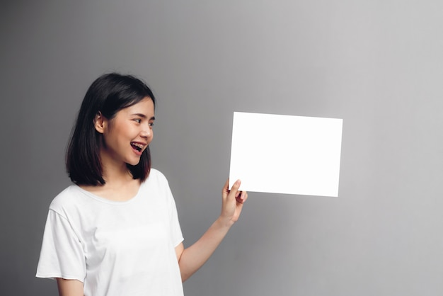 Young woman holding a blank poster for text on a white background.