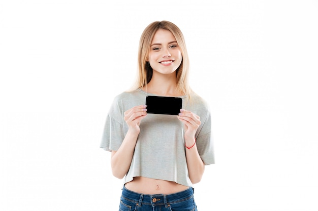 Young woman holding blank scren mobile phone and looking at camera