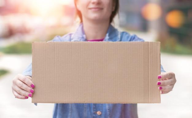 彼女の手で空白記号を保持している若い女性をクローズアップ