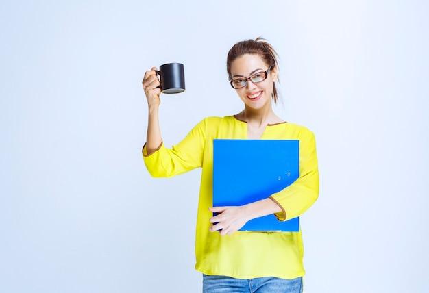 Giovane donna con in mano una cartellina blu e una tazza di bevanda nera