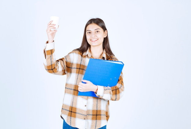 Giovane donna che tiene cartella e tazza di caffè blu sulla parete bianca.