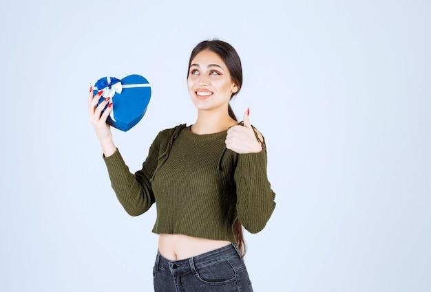 青いギフト ボックスを押しながら親指をあきらめる若い女性。