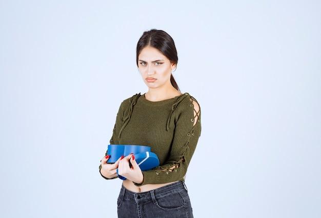 Giovane donna che tiene scatola regalo blu con espressione arrabbiata su sfondo bianco.