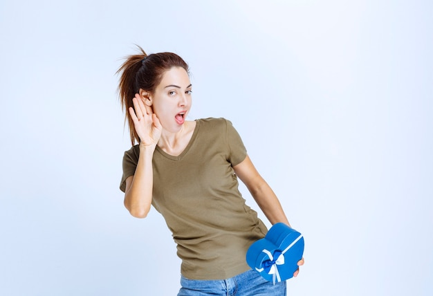Giovane donna che tiene in mano una confezione regalo a forma di orecchio blu e si sente soddisfatta