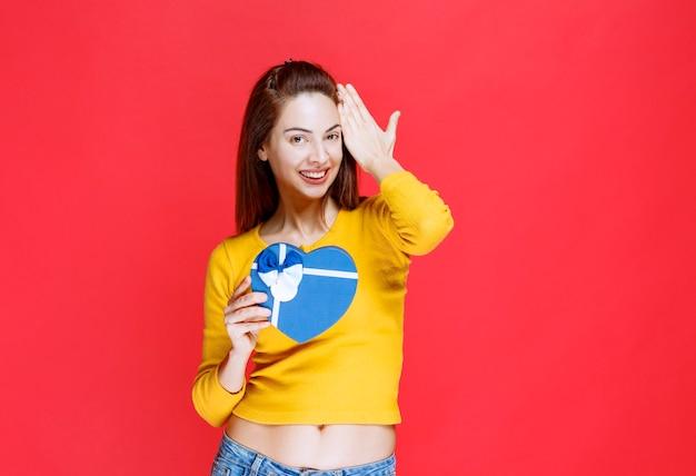 Giovane donna che tiene una confezione regalo blu a forma di cuore, sentendosi positiva e felice