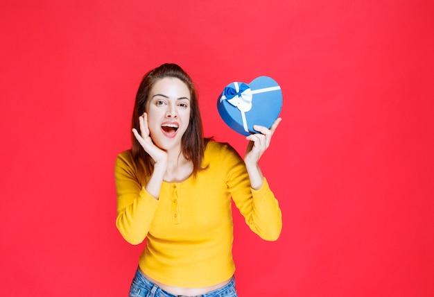 Giovane donna che tiene in mano una confezione regalo blu a forma di cuore e si sente sorpresa