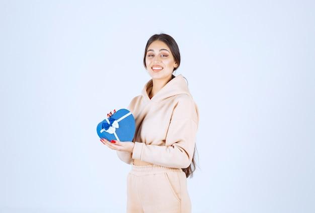 Giovane donna che tiene una confezione regalo blu a forma di cuore e sembra felice