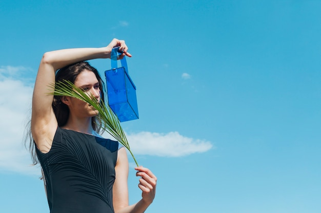 Young woman holding blue plastic bag and palm leaves in front of her face