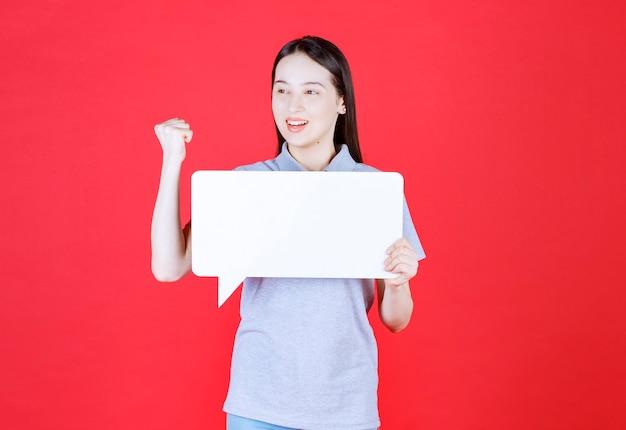 Молодая женщина держит доску и сжимает кулак