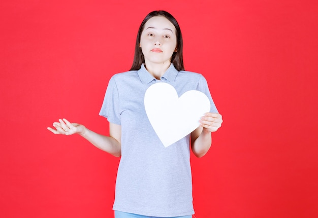 Young woman holding board in a heart shape and doesn't know what to do