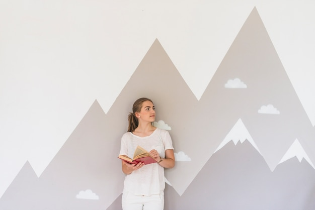 Young woman holding book standing against graffiti wall