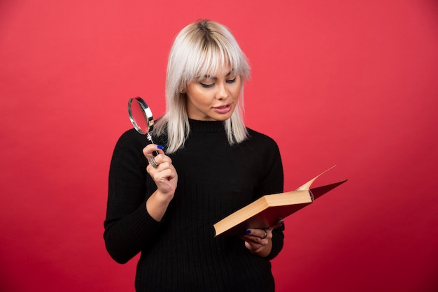 Young woman holding a book with loupe on a red wall.