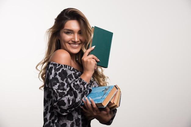 Молодая женщина, держащая книги во время смеха на белой стене.