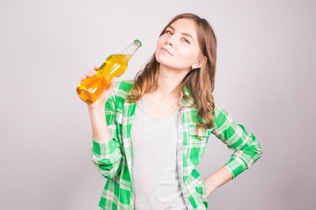 白い背景にビールのボトルを保持している若い女性
