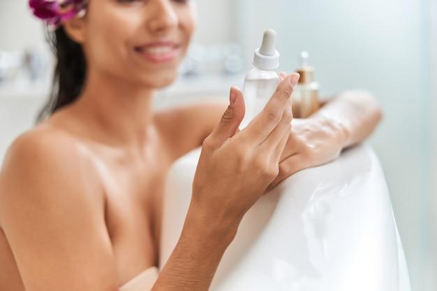 목욕하는 동안 비타민 세럼 한 병을 들고 있는 젊은 여성