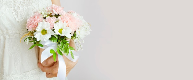 Young woman holding bouquet of flowers in a white dress on a light grey background. woman with a flowers in a basket with a ribbon.