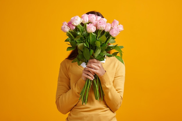 Young woman holding bouquet of roses, yellow background. female person got a surprise, event or birthday celebration, flower gift