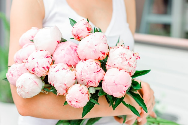 Young woman holding bouquet of white pink peonies in street