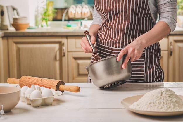 生地と泡立て器、クローズアップとボウルを保持している若い女性。縞模様のエプロンを着た女性がキッチンで料理をしている