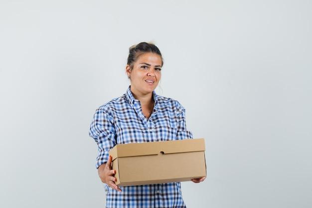 市松模様のシャツのボックスを保持している若い女性。