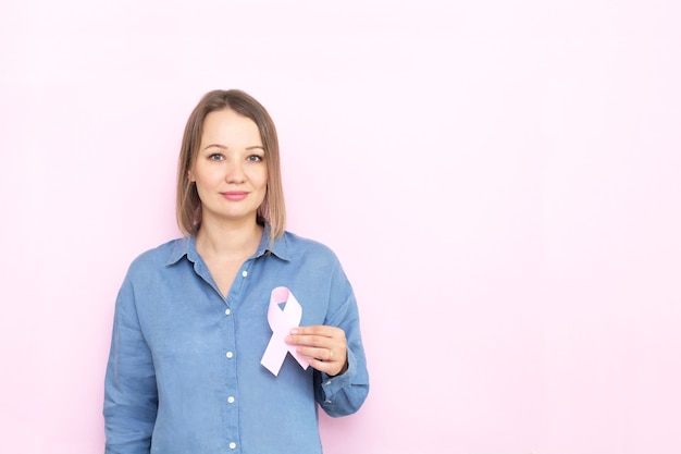 Young woman holding brest cancer ribbon over pink background.