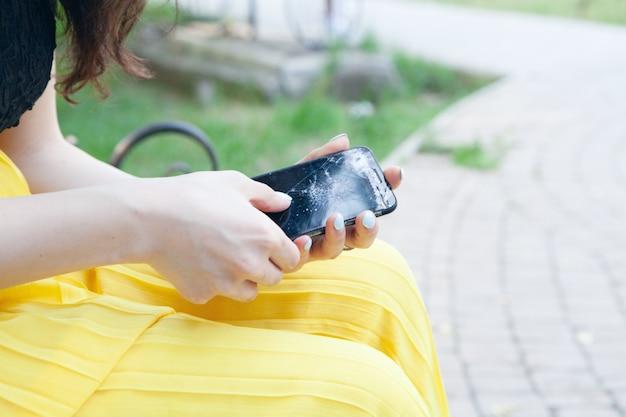 公園で壊れた電話を保持している若い女性